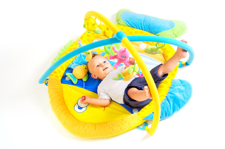 One year old  boy enjoys playing with toys. Studio Shot. All toys visible on the photo are officialy property released. Stock Photo - 1414194