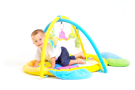 One year old  boy enjoys playing with toys. Studio Shot. All toys visible on the photo are officialy property released. Stock Photo - 1414140