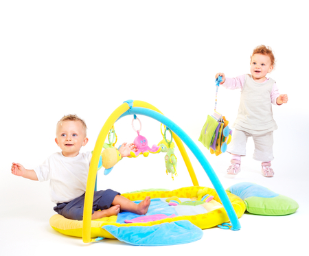 One year old  (a boy and a girl) enjoy playing with toys. Studio Shot. All toys visible on the photo are officialy property released. Stock Photo - 1414165