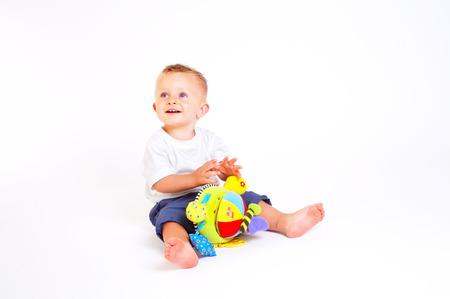 One year old  boy enjoys playing with toys. Studio Shot. All toys visible on the photo are officialy property released. Stock Photo - 1414129