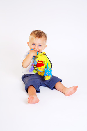 One year old  boy enjoys playing with toys. Studio Shot. All toys visible on the photo are officialy property released. Stock Photo - 1414171