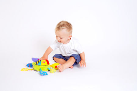 One year old  boy enjoys playing with toys. Studio Shot. All toys visible on the photo are officialy property released. Stock Photo - 1414154