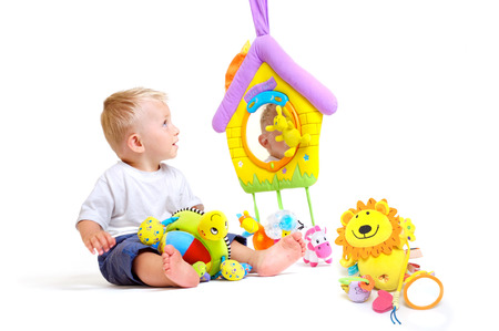 One year old  boy enjoys playing with toys. Studio Shot. All toys visible on the photo are officialy property released. Stock Photo - 1414147