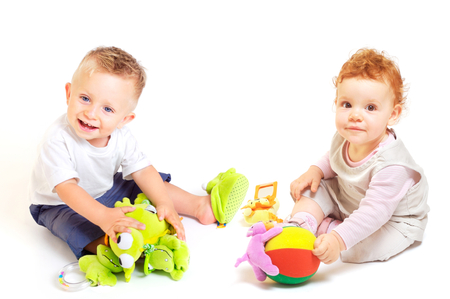 One year old  (a boy and a girl) enjoy playing with toys. Studio Shot. All toys visible on the photo are officialy property released. Stock Photo - 1414153