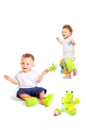 all one: One year old  (a boy and a girl) enjoy playing with toys. Studio Shot. All toys visible on the photo are officialy property released.