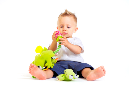 One year old  boy enjoys playing with toys. Studio Shot. All toys visible on the photo are officialy property released. Stock Photo - 1414132