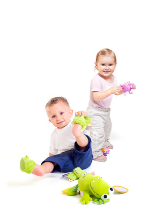 One year old  (a boy and a girl) enjoy playing with toys. Studio Shot. All toys visible on the photo are officialy property released.