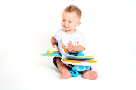 all in one: One year old  boy enjoys playing with toys. Studio Shot. All toys visible on the photo are officialy property released.
