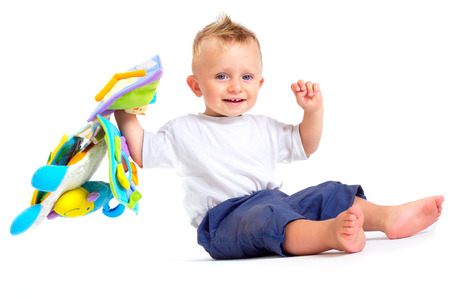 One year old  boy enjoys playing with toys. Studio Shot. All toys visible on the photo are officialy property released. Stock Photo - 1414155