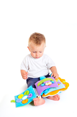 One year old  boy enjoys playing with toys. Studio Shot. All toys visible on the photo are officialy property released. photo