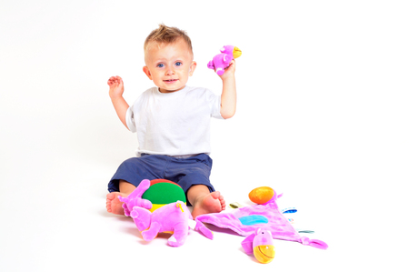 One year old  boy enjoys playing with toys. Studio Shot. All toys visible on the photo are officialy property released. Stock Photo - 1414138
