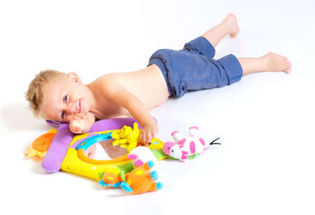 One year old  boy enjoys playing with toys. Studio Shot. All toys visible on the photo are officialy property released. Stock Photo - 1414157