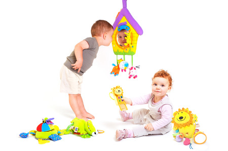 two years: Two years old  boy and a one year old girl enjoy playing with toys. Studio Shot. All toys visible on the photo are officialy property released.