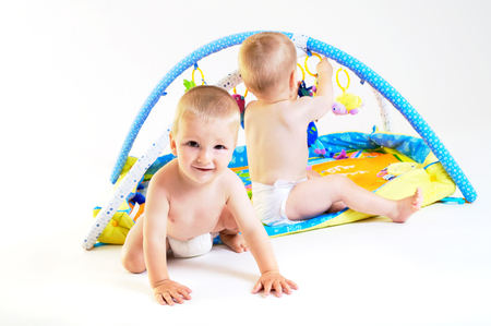 Twin baby boys are plaing together. Studio shot. All toys visible on the photo are officialy property released. Stock Photo