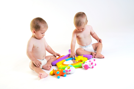 Twin baby boys are plaing together. Studio shot. All toys visible on the photo are officialy property released. Stock Photo - 1414408