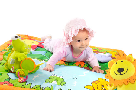 8 months old baby girl enjoy playing with soft baby toys. Studio shot. All toys visible on the photo are officialy property released. Stock Photo - 1414196