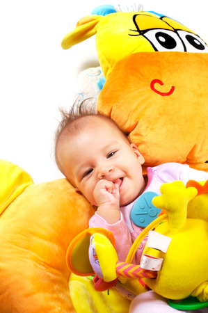 8 months old baby girl enjoy playing with soft baby toys. Studio shot. All toys visible on the photo are officialy property released. Stock Photo - 1414311