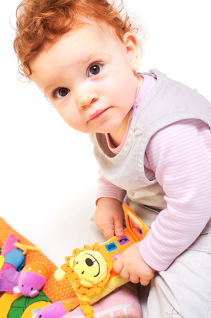One year old red haired baby girl plays with toys. Studio Shot. All toys visible on the photo are officialy property released. Stock Photo - 1422480