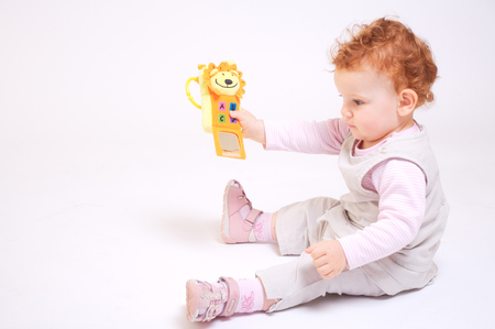 One year old red haired  girl plays with toys. Studio Shot. All toys visible on the photo are officialy property released. Stock Photo - 1414187