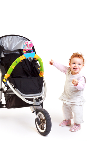 One year old red haired  girl with  stroller. Studio Shot. All toys visible on the photo are officialy property released. Stock Photo - 1414162