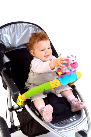 One year old red haired baby girl with baby stroller. Studio Shot. All toys visible on the photo are officialy property released. Stock Photo - 1422465
