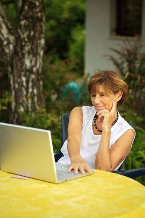 sinecure: Modern senior woman sitting in the garden at home and using a laptop computer. Summer, outdoor.