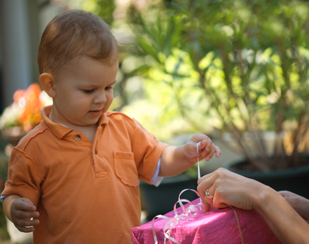 two years: Two years old baby boy helps his mother unpack a gift. Outdoor.