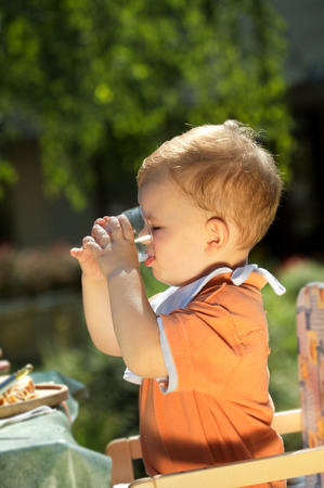 two years: Two years old  boy drinking.  BBQ party outdoor, in the garden.