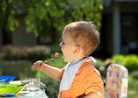 two years: Two years old  boy eating.  BBQ party outdoor, in the garden.