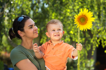 Two years old  boy and mother enjoy the summer together, playing with a sunflower in the garden. Outdoor, sunlight. photo