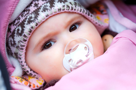 A few months old baby outdoor in warm clothes in a cold winter day. photo