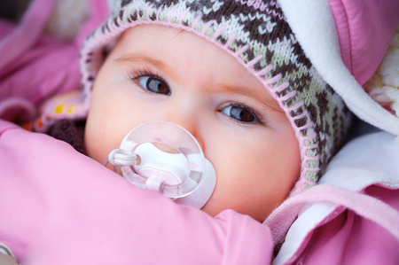 A few months old baby outdoor in warm clothes in a cold winter day. Stock Photo - 1431914