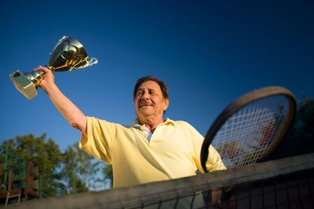 Active senior man in his 70s is posing on the tennis court with cups in hands. Outdoor, sunlight. photo