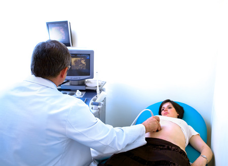 Obstetrician examining pregnant belly by 4D ultrasonic scan. Stock Photo