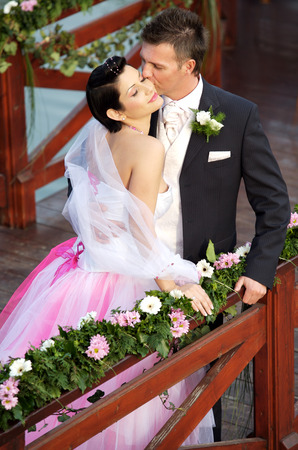 Young couple on a formal wedding photo. The groom kisses his bride while her eyes are closed. Stock Photo - 1422522
