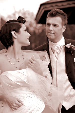 manhood: Bride and groom standing side by side outdoors, smiling, portrait
