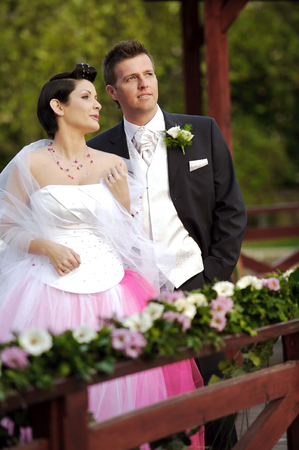 Bride and groom standing side by side outdoors, smiling, portrait photo