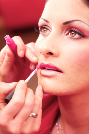 Close up of beautician creating makeup for a young women in the beauty parlour. Stock Photo - 1414261