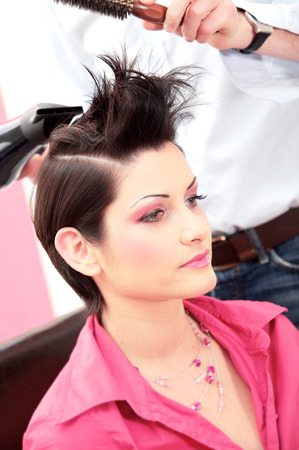 Beautiful young woman gets a hairdo in the beauty-shop.
