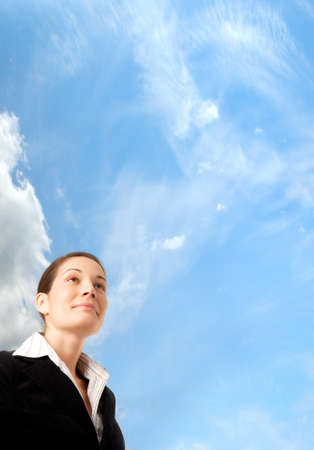 buiding: Young and ambitious businesswoman looks at the future in front of the blue sky.