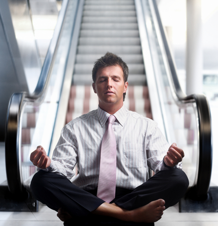 Businessman meditating in lotus position in front of an escalator indoor. photo