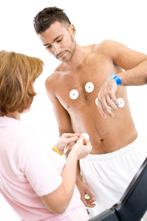 not ready: Nurse makes the patient ready for medical EKG test. Real people, real locacion, not a staged photo with models.