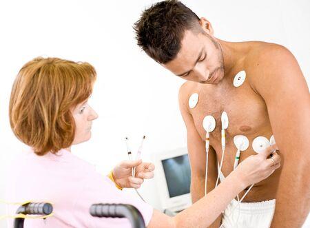 electrocardiogram: Infermiere rende il paziente pronto per la prova medica ECG. REAL PEOPLE, REAL locacion, non una fotografia di scena con modelli.
