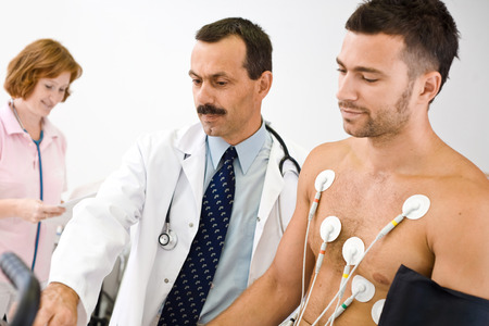 Medical team performing an EKG test on  young male patient. Real people, real locacion, not a staged photo with models. Focus is placed on the  doctor. Stock Photo - 1575702