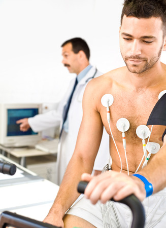 electrocardiograma: Doctor realizando una prueba de EKG en j�venes de sexo masculino paciente. Personas reales, locacion real, no una escena de fotos con modelos.