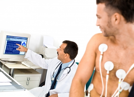 ekg: Doctor performing an EKG test on young male patient. Real people, real locacion, not a staged photo with models.