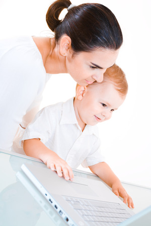 2 years old: Mother and 2 years old  boy sitting at the desk and using laptop computer. Stock Photo