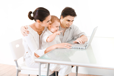 sinecure: Family with 2 years old  boy sitting at the desk and using laptop computer.