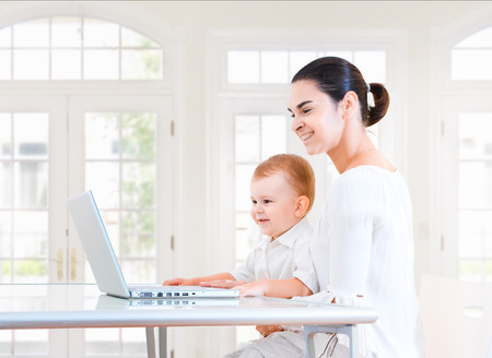 sinecure: Mother and 2 years old  boy sitting at the desk and using laptop computer. Indoor, brightly lit. Stock Photo
