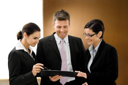 Well dresses business people talking and looking at a file in font of an executive wooden backgrond. Stock Photo - 1738694